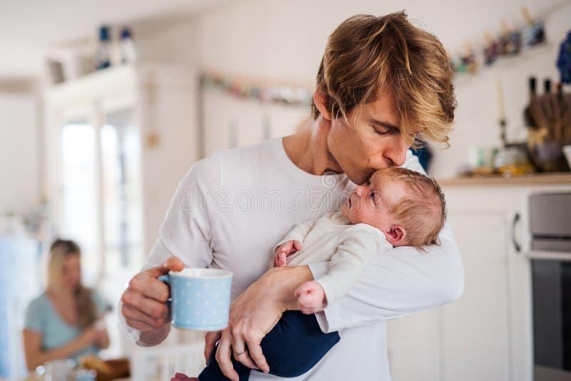Pai novo que guarda um bebê recém-nascido na cozinha em casa, beijando fotos de stock