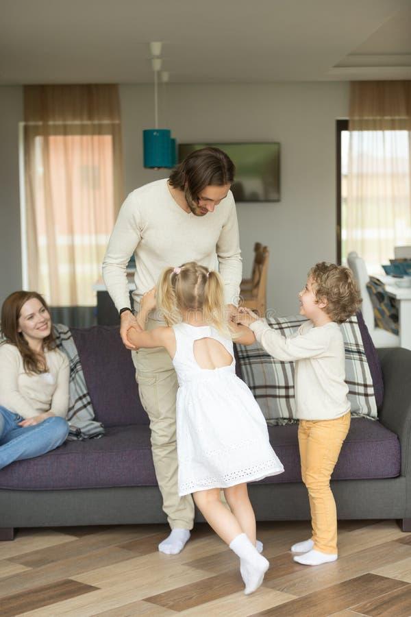 Pai novo que joga com filho e filha em casa, vertical imagens de stock