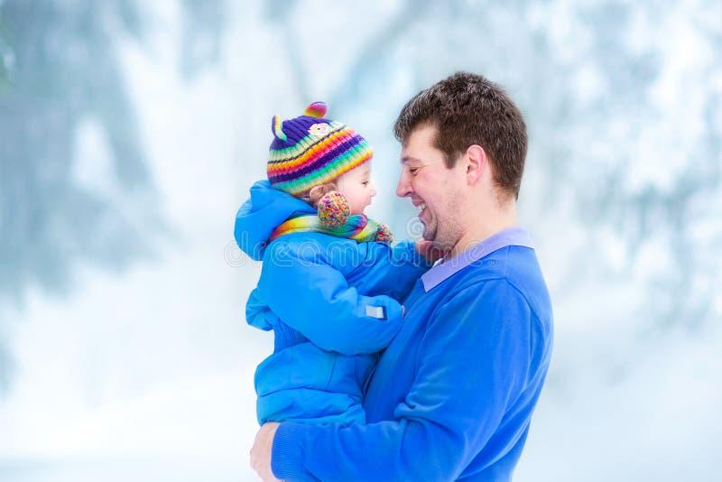 Pai novo que joga com o bebê engraçado no parque nevado fotografia de stock