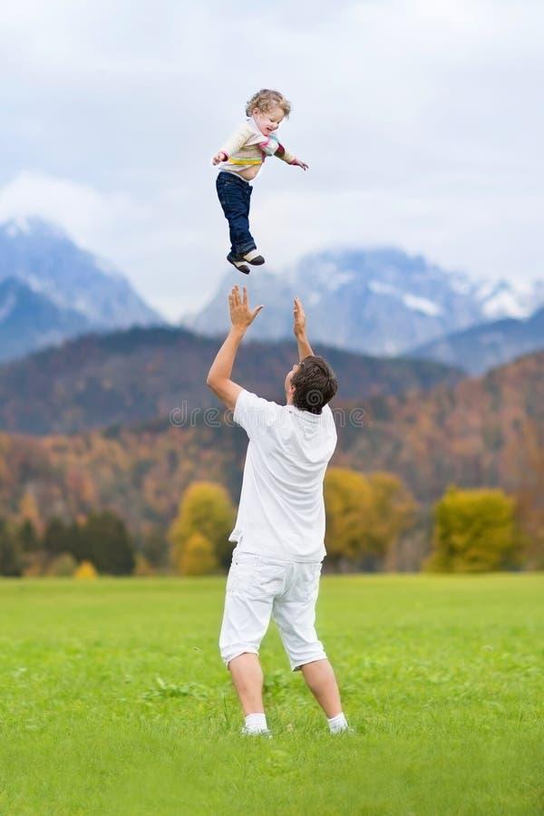 Pai novo que joga sua elevação do bebê no céu imagens de stock