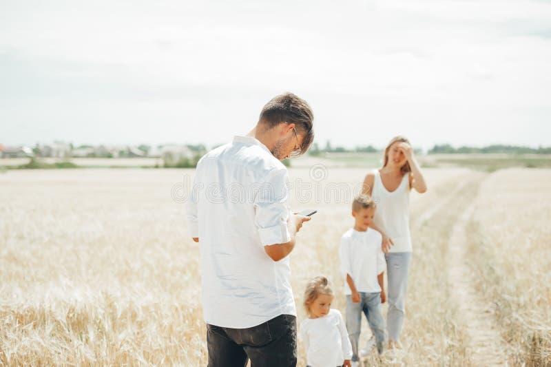 Pai novo que olha algo no telefone esperto que dá uma volta junto com a família em um campo de trigo imagens de stock royalty free