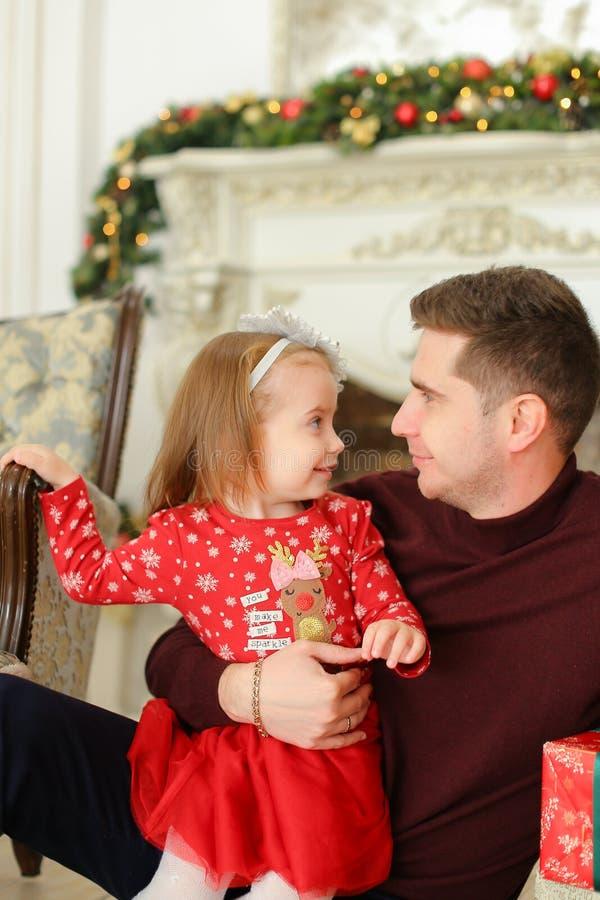 Pai novo que senta-se com a chaminé decorada próxima da filha pequena e que mantém presentes fotos de stock royalty free