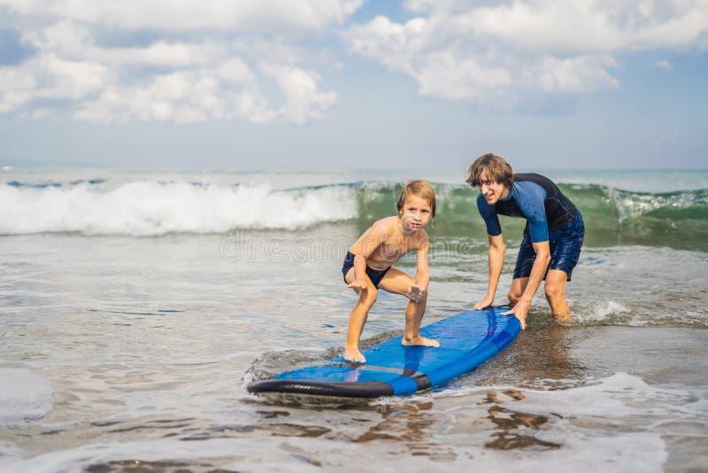 Pai ou instrutor que ensinam a seu filho da criança de 4 anos como surfar dentro fotografia de stock