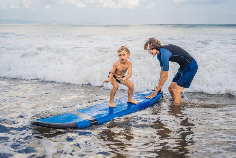 Pai ou instrutor que ensinam a seu filho da criança de 4 anos como surfar dentro foto de stock royalty free