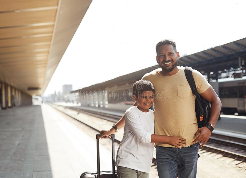 Pai positivo e filho hindu que estão na plataforma railway foto de stock royalty free