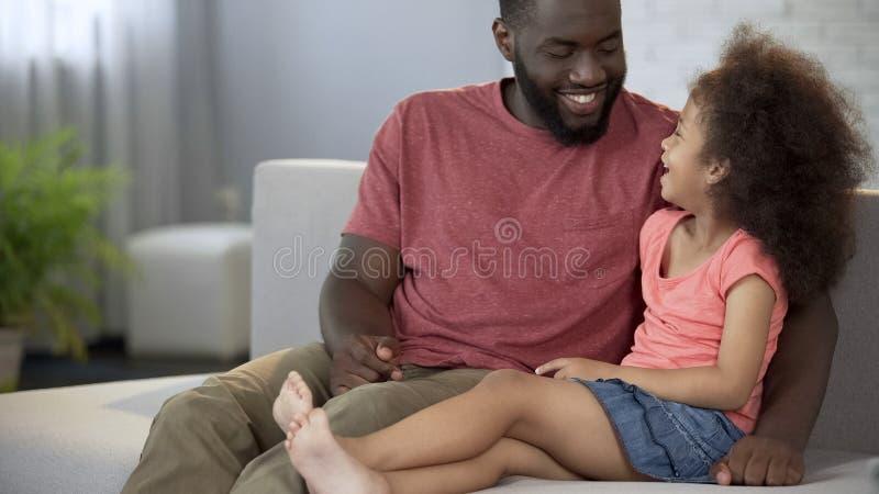 Pai preto e filha que riem, passando o tempo junto, família amigável foto de stock