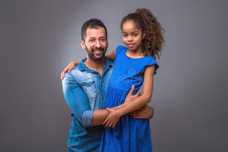 Pai preto novo que abraça sua filha adolescente fotos de stock