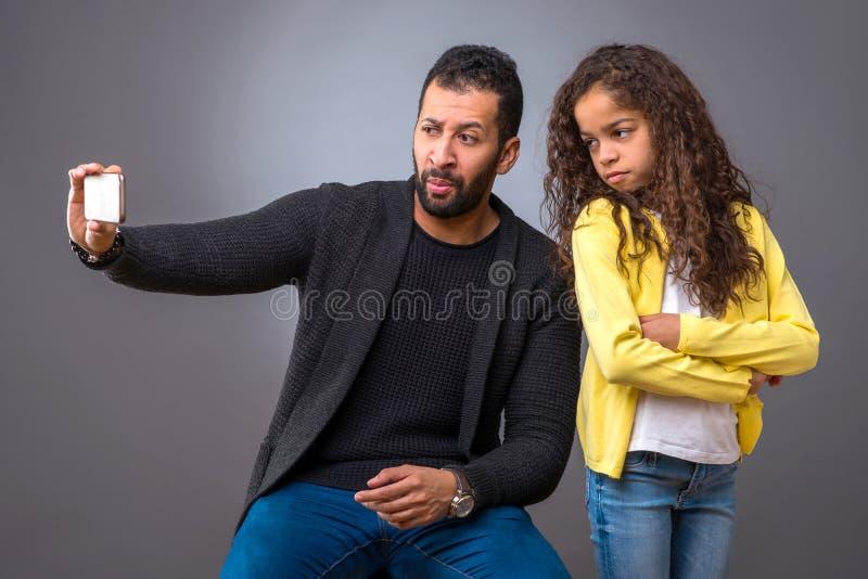 Pai preto que toma o selfie com sua filha foto de stock