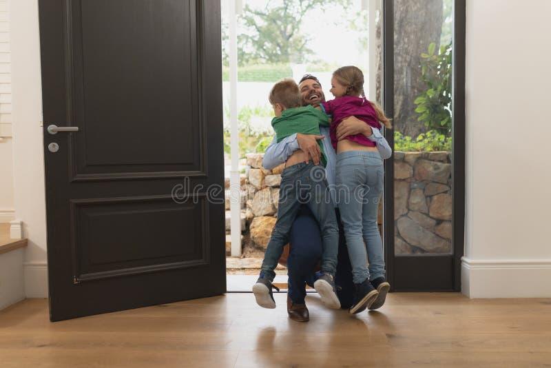 Pai que abraça suas crianças como entra na casa foto de stock