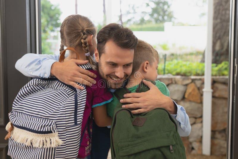 Pai que abraça suas crianças na porta em uma casa confortável fotos de stock