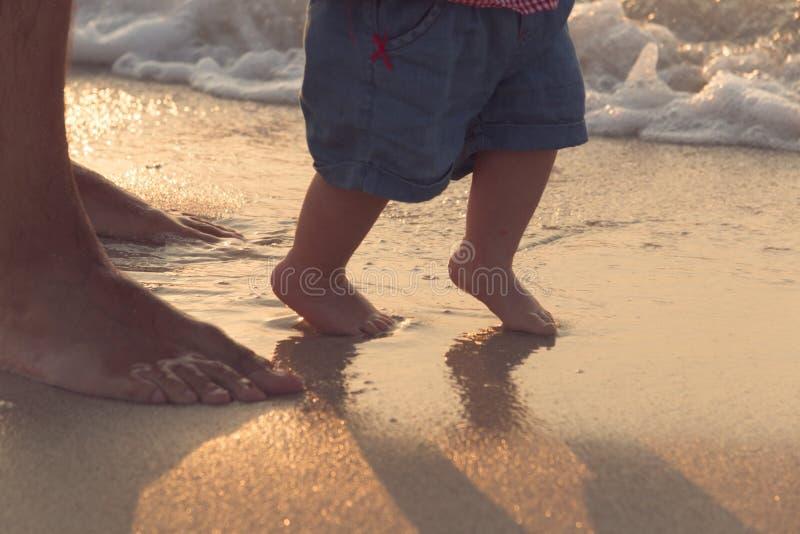 Pai que ajuda seu bebê com as primeiras etapas, bebê de ensino a andar o conceito, foto cândido exterior na praia, despesa imagem de stock royalty free