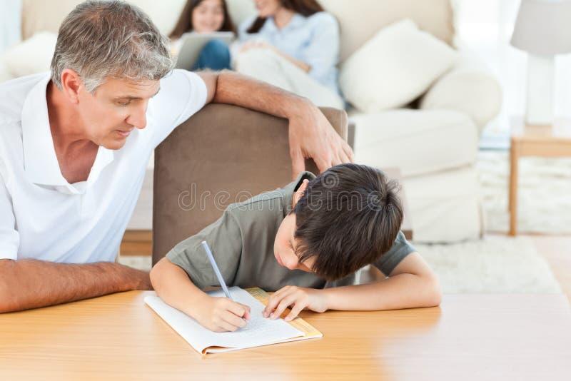 Pai que ajuda seu filho com seus trabalhos de casa fotografia de stock