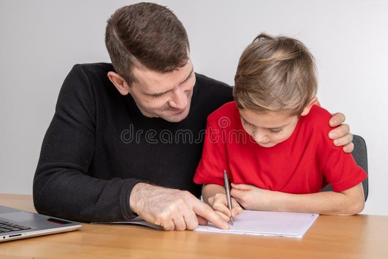 Pai que ajuda seu filho com trabalhos de casa imagem de stock royalty free