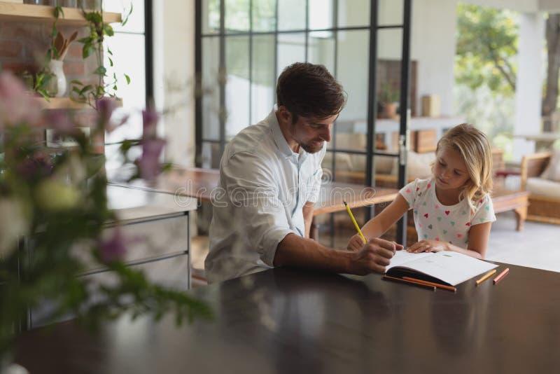 Pai que ajuda sua filha com trabalhos de casa em uma casa confortável imagem de stock royalty free