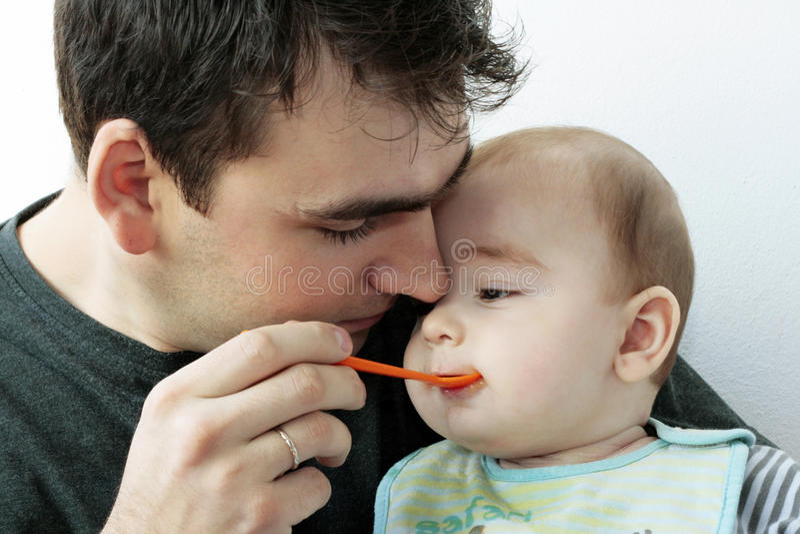 Pai que alimenta seu bebê pequeno fotos de stock