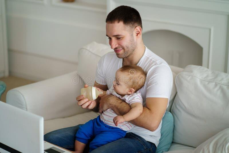 Pai que alimenta seu filho pequeno da garrafa fotografia de stock
