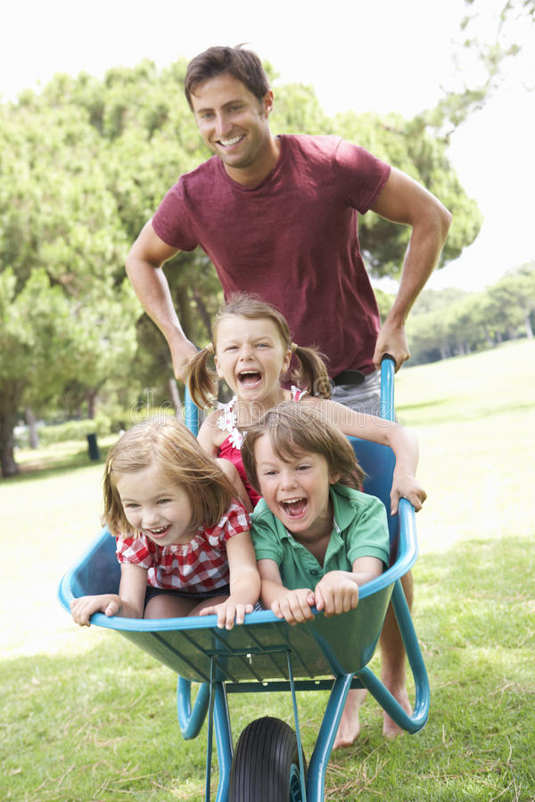 Pai que dá a crianças o passeio no Wheelbarrow fotografia de stock