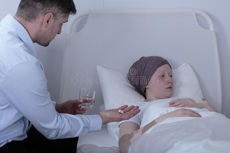 Pai que dá medicinas doentes da filha fotos de stock royalty free