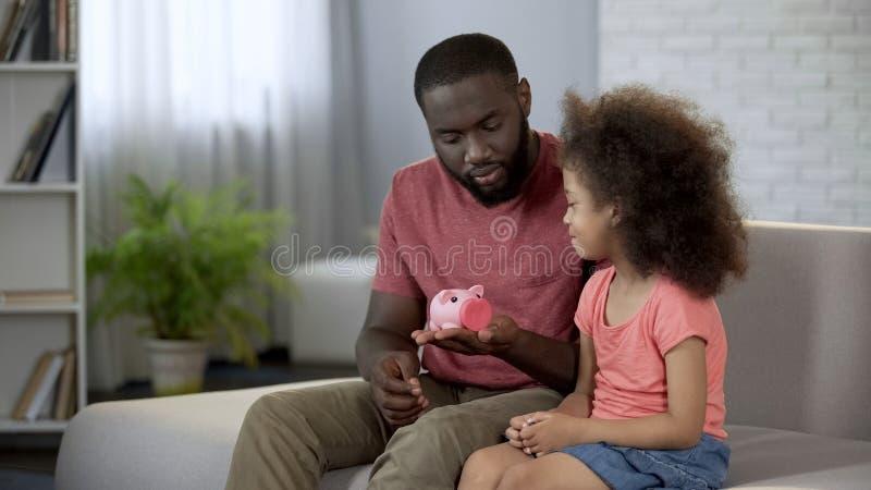 Pai que dá o mealheiro a pouca filha, criança de ensino para salvar o dinheiro foto de stock royalty free