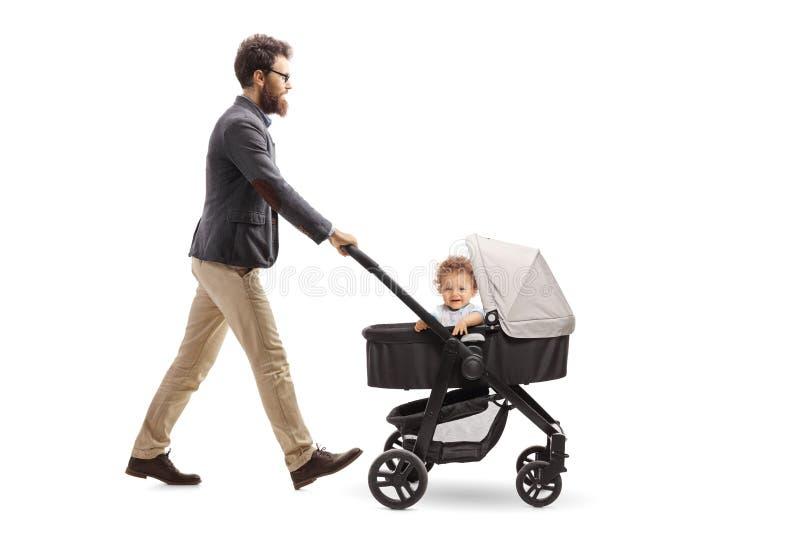 Pai que empurra um carrinho de criança de bebê imagem de stock