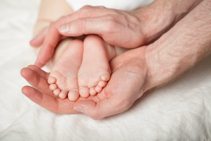 Pai que guarda babyfeets rec?m-nascidos em suas m?os no fundo branco foto de stock