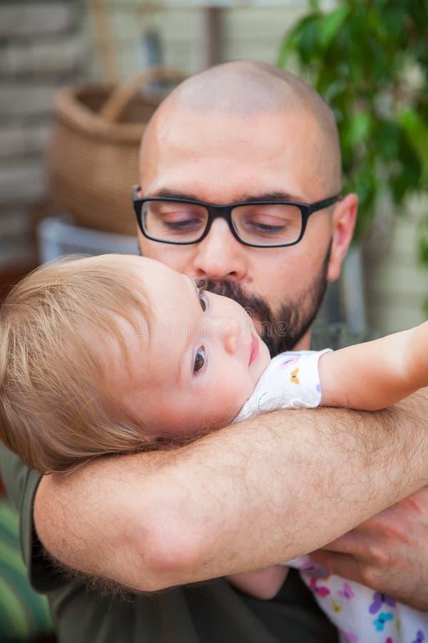Pai que guarda e que beija seu bebê foto de stock