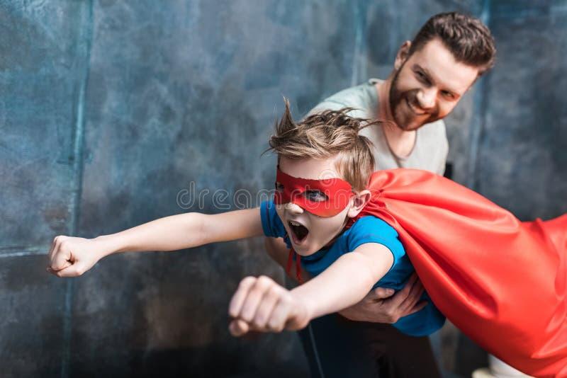 Pai que guarda o filho no voo do traje do super-herói foto de stock