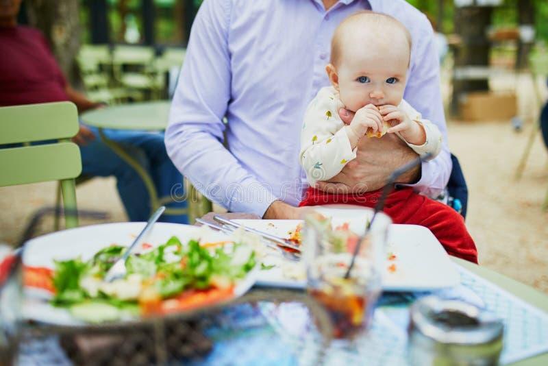 Pai que guarda sua filha no regaço ao comer no restaurante imagem de stock