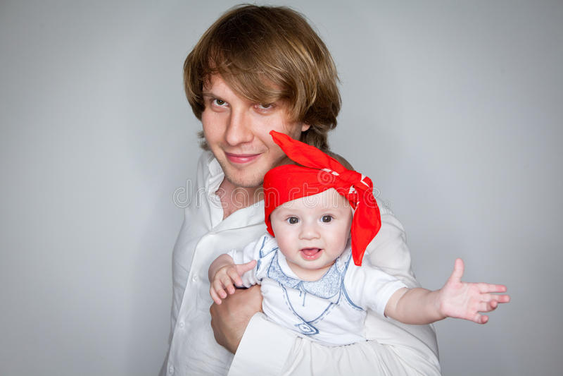 Pai que guarda uma criança de sete meses foto de stock