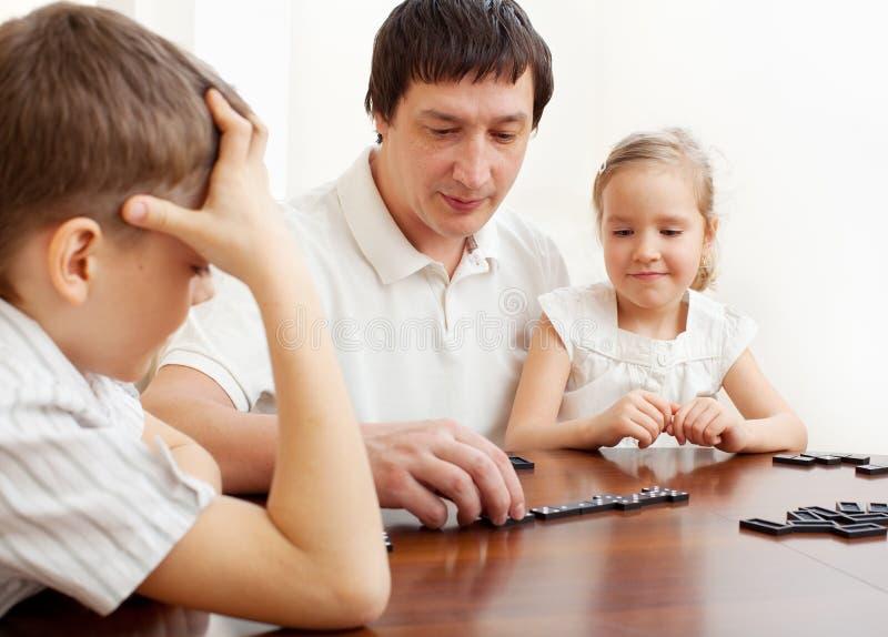 Pai que joga com crianças em casa foto de stock
