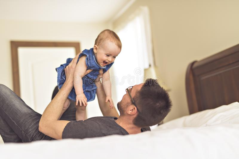 Pai que joga com seu bebê no quarto fotos de stock