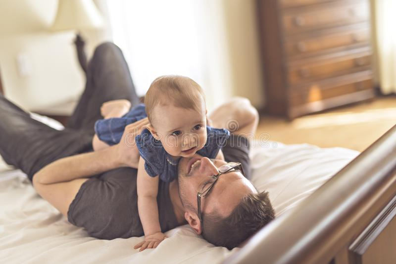 Pai que joga com seu bebê no quarto fotografia de stock