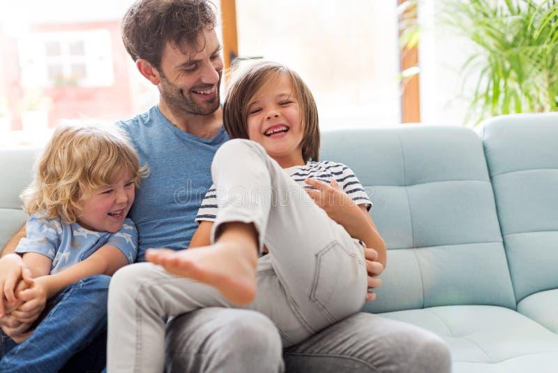 Pai que joga com suas crian?as em casa imagem de stock