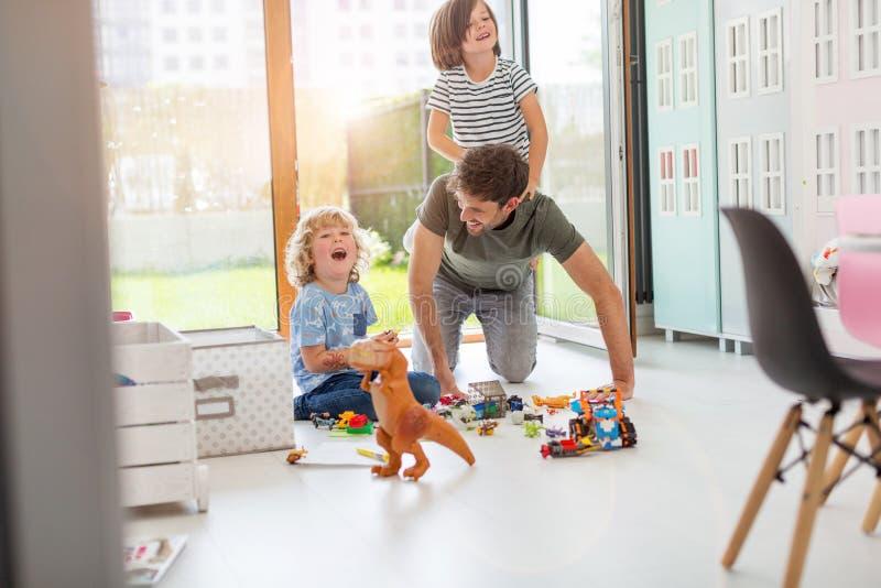 Pai que joga com suas crian?as em casa imagem de stock royalty free