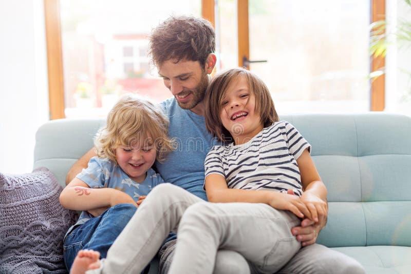 Pai que joga com suas crian?as em casa fotografia de stock royalty free