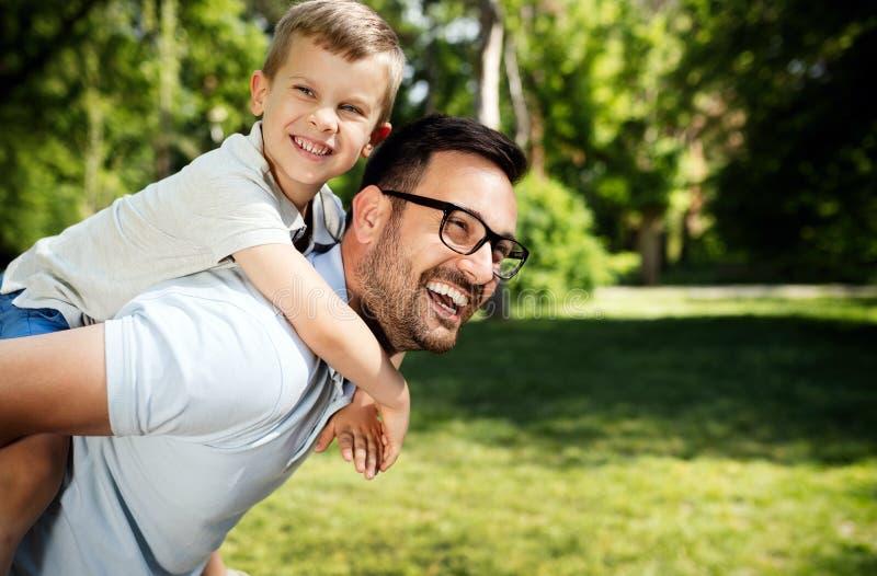 Pai que leva seu filho no ar livre traseiro e sorrindo fotografia de stock royalty free
