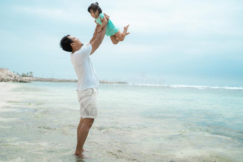 Pai que levanta sua filha que joga na praia imagens de stock