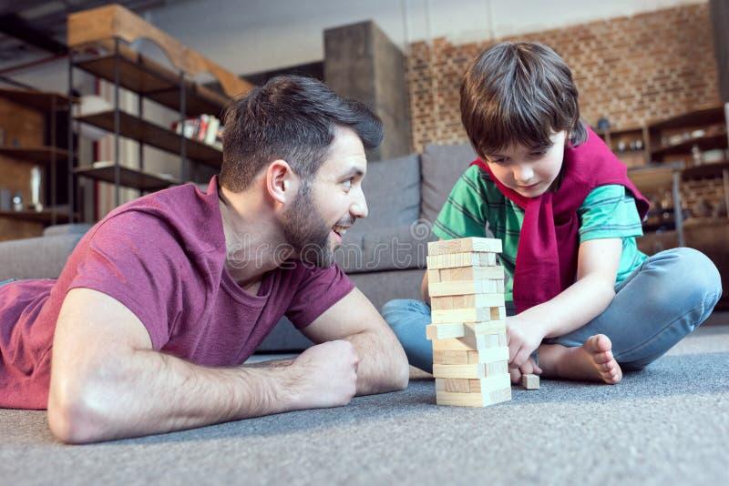 Pai que olha o filho que joga o jogo do jenga fotos de stock royalty free