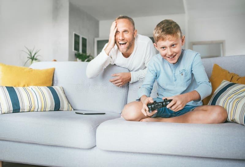 Pai que olha seu filho jogar o jogo de vídeo da tevê usando o gamepad fotos de stock