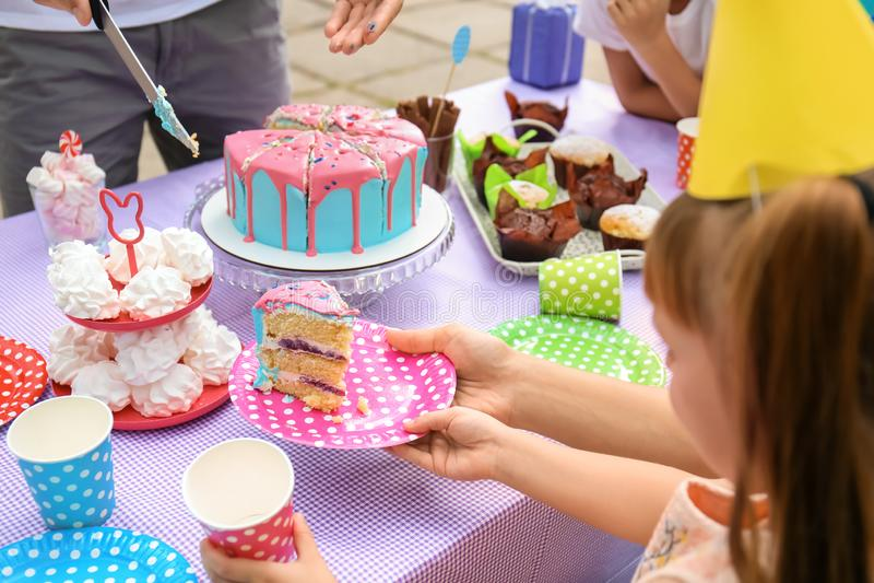 Pai que põe o pedaço de bolo na placa da filha na festa de anos fora fotos de stock royalty free