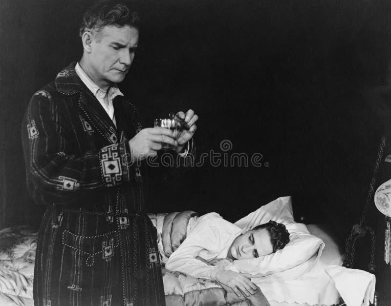 Pai que prepara a medicina para o filho doente (todas as pessoas descritas não são umas vivas mais longo e nenhuma propriedade ex fotos de stock royalty free