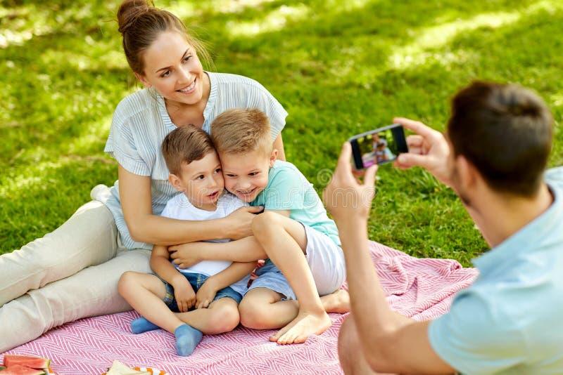 Pai que toma a imagem da família no piquenique no parque foto de stock royalty free