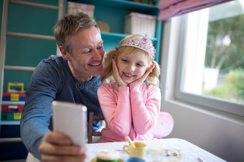 Pai que toma um selfie de seu vestir da filha vestido como a fada fotos de stock