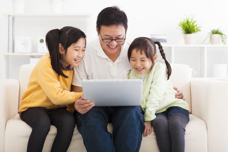 Pai que usa o portátil com meninas fotografia de stock