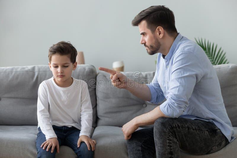 Pai raivoso repreende filho triste por mau comportamento imagens de stock