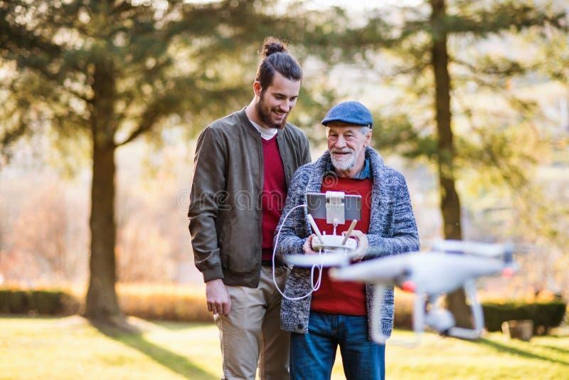 Pai sênior e seu filho com drone na natureza, falando fotos de stock