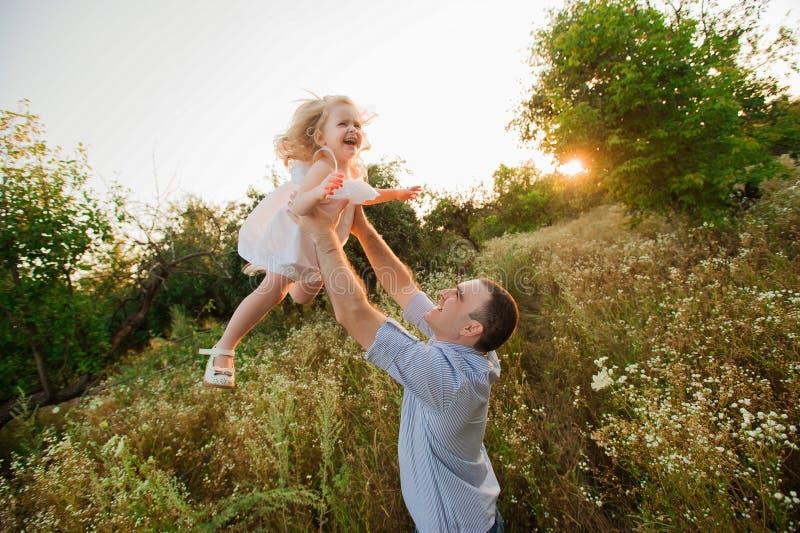 Pai saudável e filha que jogam junto no por do sol foto de stock