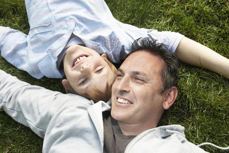Pai And Son Lying na grama imagens de stock