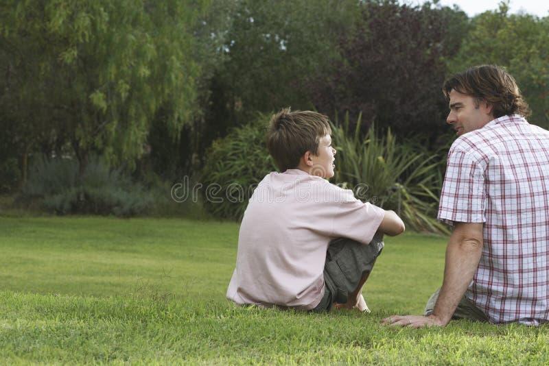Pai And Son Talking no gramado imagem de stock