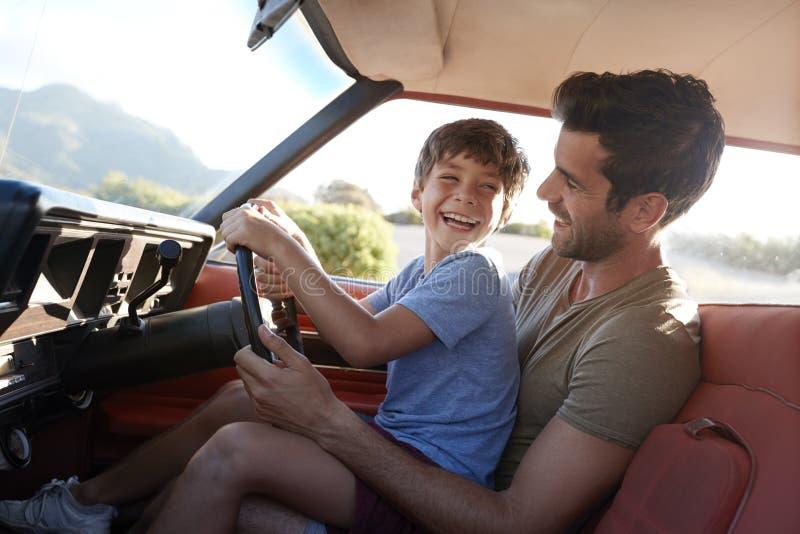 Pai Teaching Young Son para conduzir o carro na viagem por estrada fotografia de stock